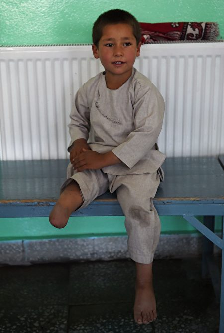 Ahmad Sayed Rahman, a five-year-old Afghan boy who lost his right leg when he was hit by a bullet in the crossfire of a battle, sits on a bench without his prosthetic leg at the International Committee of the Red Cross (ICRC) hospital for war victims and the disabled, in Kabul on May 7, 2019. - With his hands in the air and an infectious grin spreading from ear to ear, a young Afghan boy whirls around a Kabul hospital room on his new prosthetic leg. The boy, five-year-old Ahmad Sayed Rahman, has become a social media star in Afghanistan and beyond after a short video of him effortlessly dancing on his new limb was published this week on Twitter. (Photo by WAKIL KOHSAR / AFP) (Photo credit should read WAKIL KOHSAR/AFP/Getty Images)