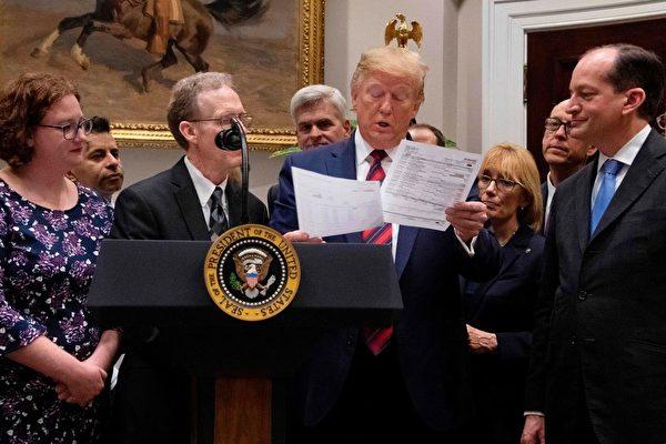美国总统川普5月9日在白宫发表意外医疗账单事件的讲话期间,查看医疗法案。(Jim Watson/AFP/Getty Images)