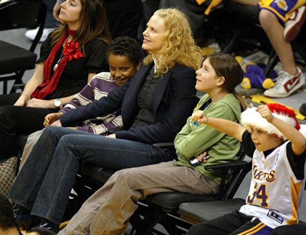 2004年12月25日,妮可基嫚(中)和养子康纳(左中)和养女伊莎贝拉(右二)在洛杉矶观看NBA赛事。(Matthew Simmons/Getty Images)