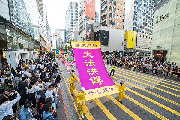 5月12日,香港法轮功学员举行集会游行庆祝世界法轮大法日。图为游行队伍途经尖沙咀广东道,大批游客和市民夹道观看,纷纷拍下盛大的游行场面。(李逸/大纪元)