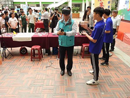 嘉義縣長翁章梁(如圖)在東吳高職攤位戴上VR,親自體驗玩虛擬實境遊戲的樂趣。