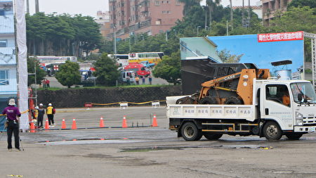 环保局车辆载进一台小山猫协助进行清理工作。