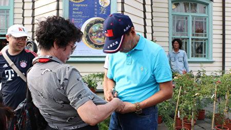 鴻海董事長郭台銘為民眾在衣服上簽名。