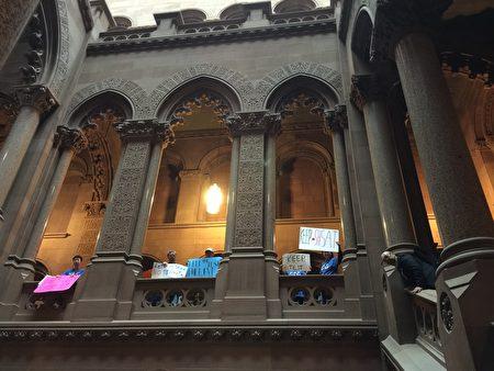 """4月30日州府奥伯尼的议会大厦中到处可见身穿""""保留SHSAT""""蓝色T恤的抗议者。"""