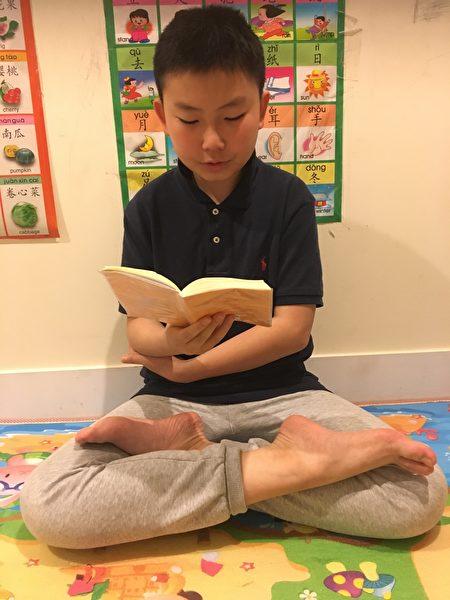 王汉在读《转法轮》。(赵芬妮/大纪元)