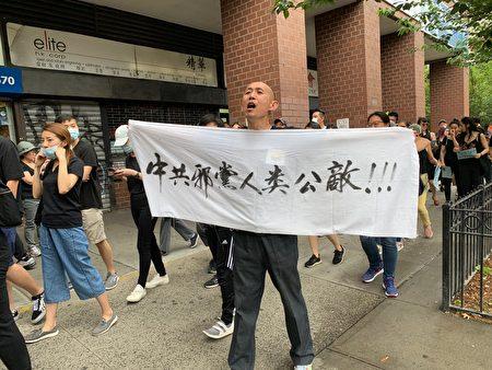 """游行者打出 """"共产邪党人类最大公敌""""的标语。"""