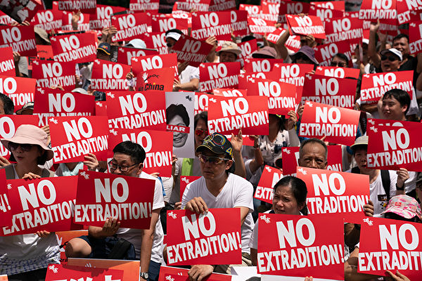HONG KONG, HONG KONG - JUNE 09: Protesters hold placards and shout slogans during a rally against the extradition law proposal on June 9, 2019 in Hong Kong China. Hundreds of thousands of protesters marched in Hong Kong in Sunday against a controversial extradition bill that would allow suspected criminals to be sent to mainland China for trial.(Photo by