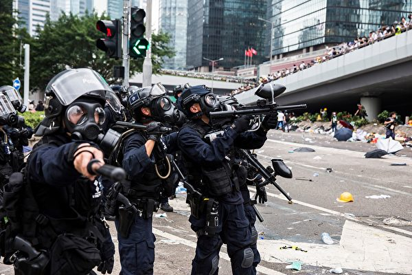 TOPSHOT - Police fire non-lethal projectiles during violent clashes against protesters in Hong Kong on June 12, 2019. - Violent clashes broke out in Hong Kong on June 12 as police tried to stop protesters storming the city's parliament, while tens of thousands of people blocked key arteries in a show of strength against government plans to allow extraditions to China. (Photo by ISAAC LAWRENCE / AFP) (Photo credit should read