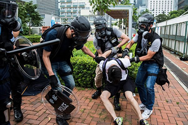 Police arrest a man (C) during violent clashes with protesters in Hong Kong on June 12, 2019. - Violent clashes broke out in Hong Kong on June 12 as police tried to stop protesters storming the city's parliament, while tens of thousands of people blocked key arteries in a show of strength against government plans to allow extraditions to China. (Photo by ISAAC LAWRENCE / AFP) (Photo credit should read