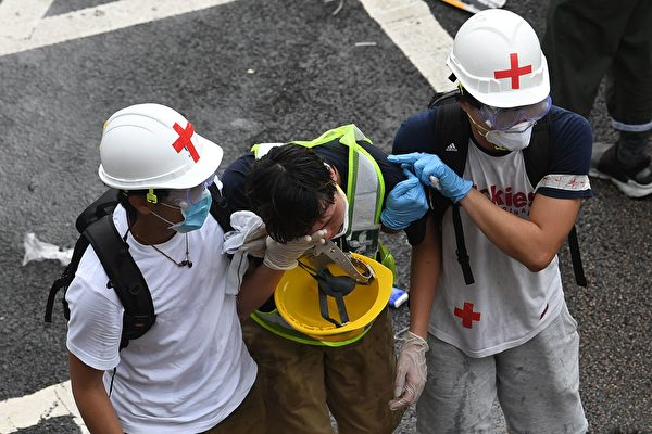 TOPSHOT - A protester is helped by medical volunteers after being hit by tear gas fired by the police during a rally against a controversial extradition law proposal in Hong Kong on June 12, 2019. - Violent clashes broke out in Hong Kong on June 12 as police tried to stop protesters storming the city's parliament, while tens of thousands of people blocked key arteries in a show of strength against government plans to allow extraditions to China. (Photo by Anthony WALLACE / AFP) (Photo credit should read