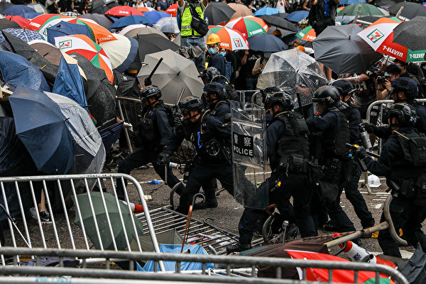 Police clash with protesters during a rally against a controversial extradition law proposal outside the government headquarters in Hong Kong on June 12, 2019. - Violent clashes broke out in Hong Kong on June 12 as police tried to stop protesters storming the city's parliament, while tens of thousands of people blocked key arteries in a show of strength against government plans to allow extraditions to China. (Photo by DALE DE LA REY / AFP) (Photo credit should read
