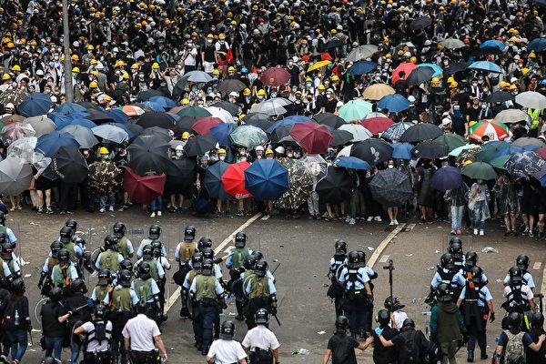 - Protesters face off with police during a rally against a controversial extradition law proposal outside the government headquarters in Hong Kong on June 12, 2019. - Violent clashes broke out in Hong Kong on June 12 as police tried to stop protesters storming the city's parliament, while tens of thousands of people blocked key arteries in a show of strength against government plans to allow extraditions to China. (Photo by DALE DE LA REY / AFP) (Photo credit should read