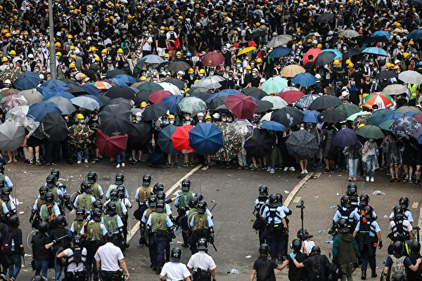 TOPSHOT - Protesters face off with police during a rally against a controversial extradition law proposal outside the government headquarters in Hong Kong on June 12, 2019. - Violent clashes broke out in Hong Kong on June 12 as police tried to stop protesters storming the city's parliament, while tens of thousands of people blocked key arteries in a show of strength against government plans to allow extraditions to China. (Photo by DALE DE LA REY / AFP) (Photo credit should read
