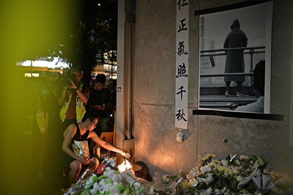 香港民眾聚在一起悼念6月15日在金鐘太古廣場、疑因情緒激動發生意外墜下的男子。(Anthony WALLACE / AFP)