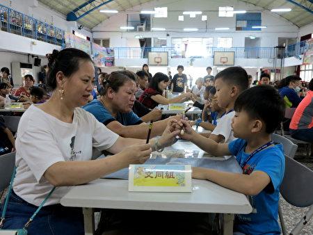 圳堵國小家長會長宋貴英,在《悠遊字在》的學習課程中與孩子一起練習用毛筆寫字。