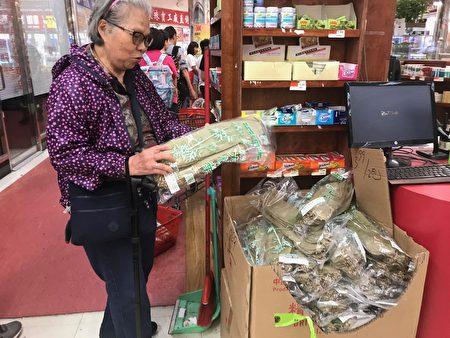 老一辈的华人保留自己在家动手包粽过节的传统,图为端午节当天一名阿婆在超市挑选包粽的竹叶。