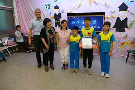 毕业生接受来宾颁奖,家长、弟妹都与有荣焉。