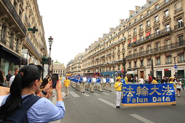 """7月20日下午,来自欧洲十几个国家的部分法轮功学员在法国巴黎举行""""纪念法轮功学员反迫害20周年""""大游行。沿途许多民众,包括大陆游客围观拍照。(章乐/大纪元)"""