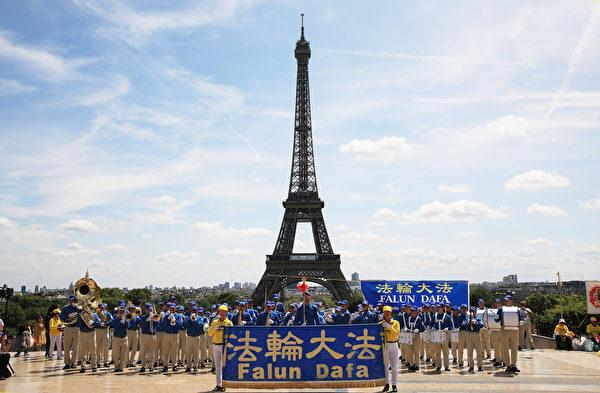 7月21日上午,歐洲天國樂團在巴黎人權廣場上演奏,吸引了過往的市民和遊客前來探尋法輪功真相。(章樂/大紀元)