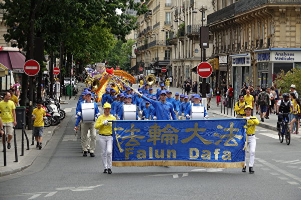 """7月20日下午,来自欧洲十几个国家的部分法轮功学员在法国巴黎举行""""纪念法轮功学员反迫害20周年""""大游行。(叶萧斌/大纪元)"""