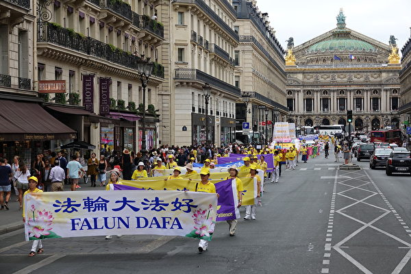 """7月20日下午,来自欧洲十几个国家的部分法轮功学员在法国巴黎举行""""纪念法轮功学员反迫害20周年""""大游行,图为游行队伍途经巴黎歌剧院。(叶萧斌/大纪元)"""