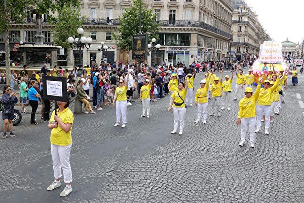 """7月20日下午,来自欧洲十几个国家的部分法轮功学员在法国巴黎举行""""纪念法轮功学员反迫害20周年""""大游行。沿途许多民众,包括大陆游客围观拍照。(叶萧斌/大纪元)"""
