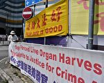 2019年4月25日,一名香港法輪功女學員在大陸遊客經常光顧的東涌調整支持法輪功的橫幅。1999年4月25日,上萬法輪功學員來到北京中南海附近的國家信訪辦和平上訪,中共政府由此發起一場迫害, 7000多萬至1億人的信仰遭到鎮壓。(Anthony WALLACE / AFP / Getty Images)
