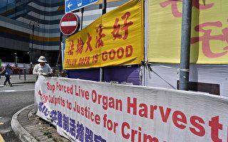 2019年4月25日,一名香港法轮功女学员在大陆游客经常光顾的东涌调整支持法轮功的横幅。1999年4月25日,上万法轮功学员来到北京中南海附近的国家信访办和平上访,中共政府由此发起一场迫害, 7000多万至1亿人的信仰遭到镇压。(Anthony WALLACE / AFP / Getty Images)