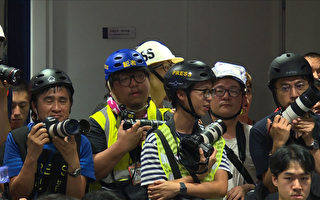 This still image taken from an AFPTV video shows Hong Kong journalists dressed in high visibility jackets and helmets during a police press conference to protest what they said was excessive force used against them during the June 12 clashes between police and protesters against a controversial extradition law proposal, in Hong Kong on June 13, 2019. - Hong Kong protest leaders announced plans for another mass rally on June 16, escalating their campaign against a China extradition bill a day after police cleared them from the streets using volleys of tear gas and rubber bullets. (Photo by AFPTV team / AFPTV / AFP) (Photo credit should read AFPTV TEAM/AFP/Getty Images)