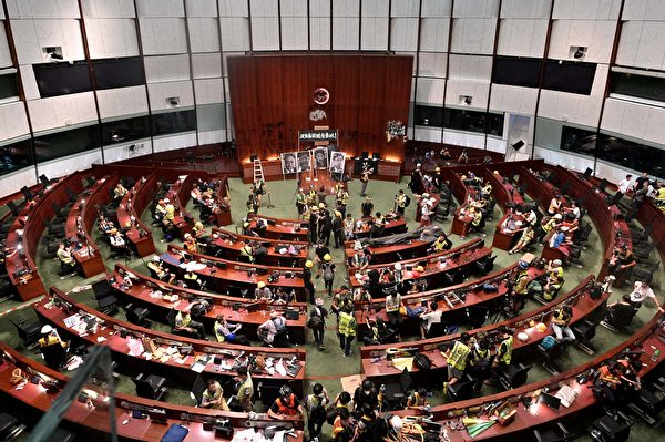 Protesters and members of the media are seen in the parliament chambers after protesters broke into the government headquarters in Hong Kong on July 1, 2019, on the 22nd anniversary of the city's handover from Britain to China. - Hundreds of protesters stormed Hong Kong's parliament late on July 1 as the territory marked its China handover anniversary, ransacking the building and daubing its walls with graffiti as the city plunged into unprecedented depths of political chaos. (Photo by Anthony WALLACE / AFP) (Photo credit should read ANTHONY WALLACE/AFP/Getty Images)