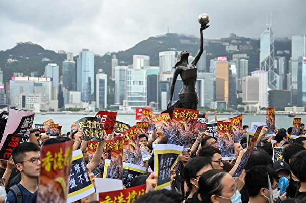 TOPSHOT - Protesters gather to take part in a march to the West Kowloon railway station, where high-speed trains depart for the Chinese mainland, during a demonstration against a proposed extradition bill in Hong Kong on July 7, 2019. - Hong Kong has been rocked by a month of huge peaceful protests as well as a series of separate violent youth-led confrontations sparked by a proposed law that would have allowed extraditions to mainland China. (Photo by Hector RETAMAL / AFP) (Photo credit should read