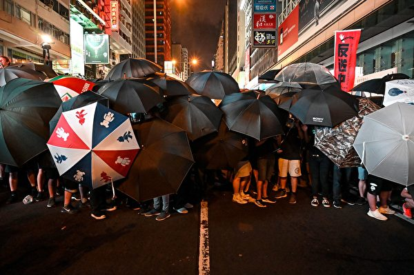 Protesters carry umbrellas to protect themselves as they face the police outside the West Kowloon railway station during a demonstration against a proposed extradition bill in Hong Kong on July 7, 2019. - Tens of thousands of anti-government protesters rallied outside a controversial train station linking the territory to the Chinese mainland on July 7, the latest mass show of anger as activists try to keep pressure on the city's pro-Beijing leaders. (Photo by Hector RETAMAL / AFP) (Photo credit should read HECTOR RETAMAL/AFP/Getty Images)