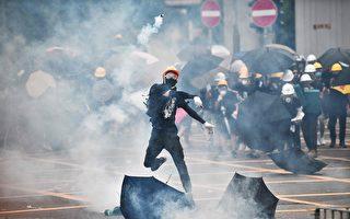 7月27日,反黑反送中的民众不顾警察反对,成千上万的民众来到元朗。图为一青年把警察发射的催泪弹扔回去。(