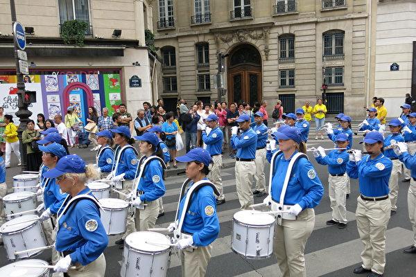 """7月20日下午,来自欧洲十几个国家的部分法轮功学员在法国巴黎举行""""纪念法轮功学员反迫害20周年""""大游行。沿途许多民众,包括大陆游客围观拍照。(关宇宁/大纪元)"""