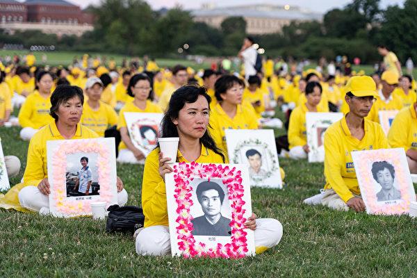 2019年7月18日,華盛頓DC,法輪功學員手持在中國大陸被迫害致死學員的遺照表達哀思。(戴兵/大紀元)