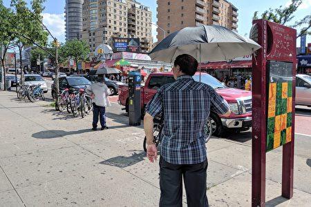 华裔耆老撑起阳伞等公车。