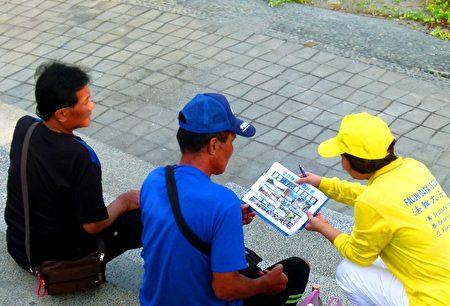 法輪功學員向遊客講真相。