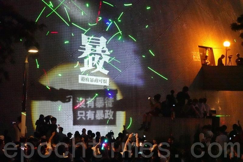 2019年8月7日,尖沙咀太空馆,民众挥舞雷射笔声援被捕的香港浸会大学学生会长方仲贤,并将抗议标语投射在太空馆的外墙上。(余钢/大纪元)