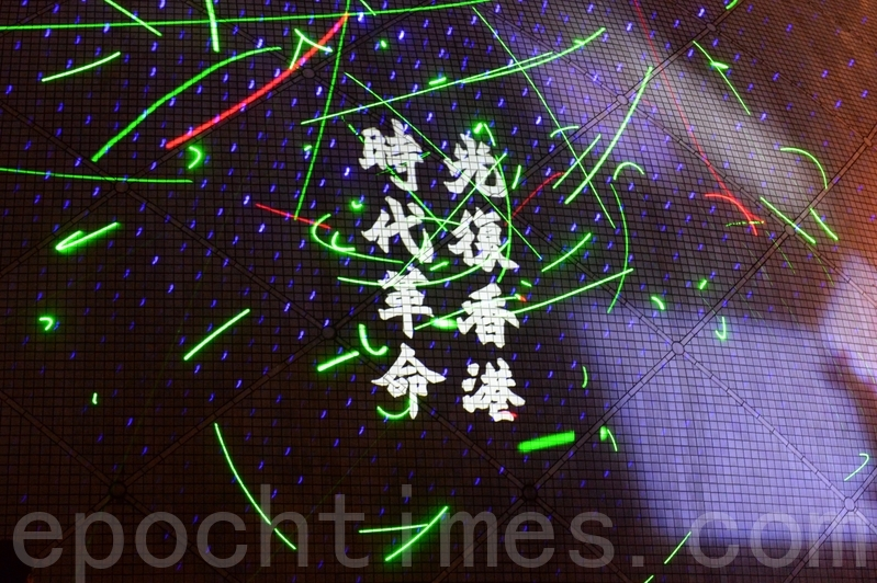 """2019年8月7日,尖沙咀太空馆,民众挥舞雷射笔声援被捕的香港浸会大学学生会长方仲贤,并将抗议标语投射在太空馆的外墙上。图为""""光复香港,时代革命""""的标语。(宋碧龙/大纪元)"""