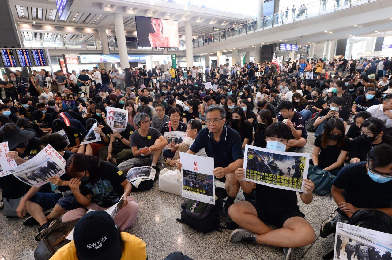 2019年8月9日,香港机场万人接机,参加者持各式海报和标语在大堂静坐。(宋碧龙/大纪元)