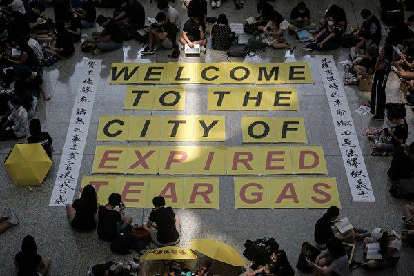 """2019年8月10日,香港机场""""万人接机""""活动进入第二天,集会人士在地上以英文拼出""""欢迎来到过期催泪瓦斯之城""""。(VIVEK PRAKASH/AFP/Getty Images)"""