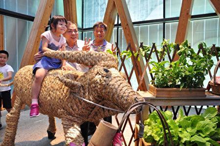 骑在草绳做的牛背上小朋友好开心,中为新竹县副县长陈见贤