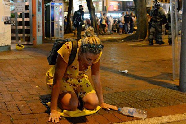 2019年8月11日夜,灣仔有一女外國人被催淚彈催到跪著。(宋碧龍/大紀元)