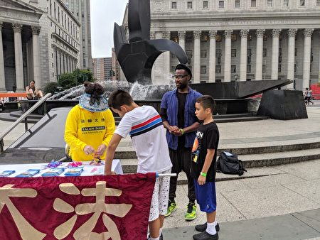 民眾向學員索要法輪功傳單和印有中英文「法輪大法好」的蓮花吊墜。