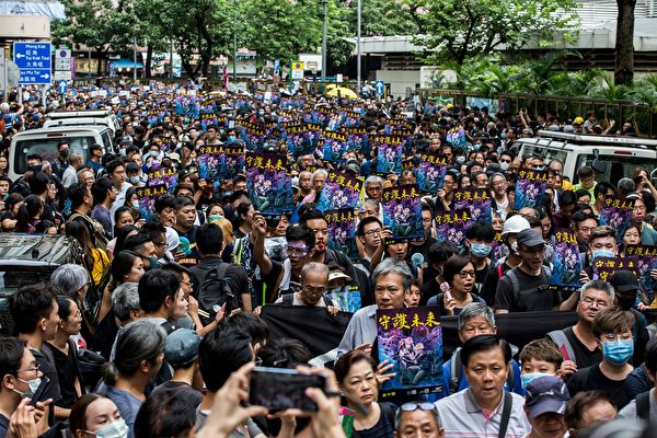 遊行市民舉著「守護未來」的海報。(ISAAC LAWRENCE / AFP/Getty Images)