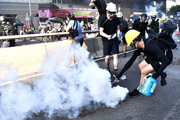 警方在金钟夏悫道一再施放催泪弹。示威者用水浇灭催泪弹。(ANTHONY WALLACE/AFP/Getty Images)