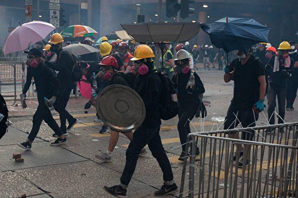 黄大仙处警方持续施放多枚催泪弹。示威者用雨伞遮挡。(ISAAC LAWRENCE/AFP/Getty Images)