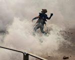 黄大仙处警方持续施放多枚催泪弹。示威者扔回催泪弹。(ISAAC LAWRENCE/AFP/Getty Images)