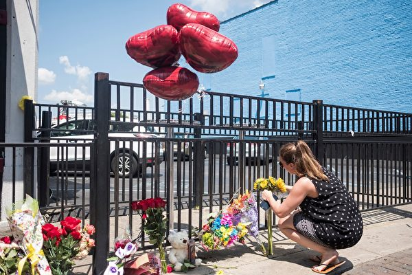 """People come to pay their respect to those who lost their lives after the mass shooting over the weekend in Dayton, Ohio on August 5, 2019. - US President Donald Trump urged Republicans and Democrats to agree on tighter gun control and suggested legislation could be linked to immigration reform after two shootings left 30 people dead and sparked accusations that his rhetoric was part of the problem. """"Republicans and Democrats must come together and get strong background checks, perhaps marrying this legislation with desperately needed immigration reform,"""" Trump tweeted as he prepared to address the nation on two weekend shootings in Texas and Ohio. """"We must have something good, if not GREAT, come out of these two tragic events!"""" Trump wrote. (Photo by Megan JELINGER / AFP)        (Photo credit should read MEGAN JELINGER/AFP/Getty Images)"""