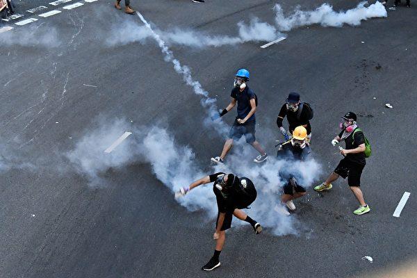 大圍美田路一帶警察施放多枚催淚彈。圖為示威者扔回催淚彈。(ANTHONY WALLACE/AFP/Getty Images)
